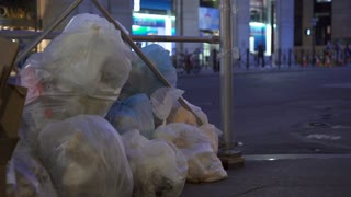 Trash bags stacked up on city sidewalks at night 4k