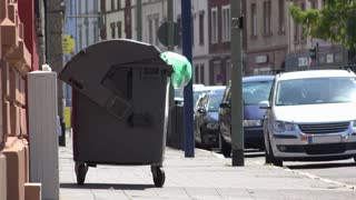 Trash can dumpster on side of city street in Europe 4k