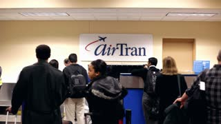 Travelers standing at Airtran desk