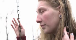 Troubled young girl looking into the distance hanging on swing 4k