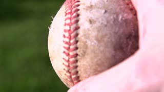 Turning baseball in hand slow motion