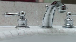 Turning on water faucet in bathroom