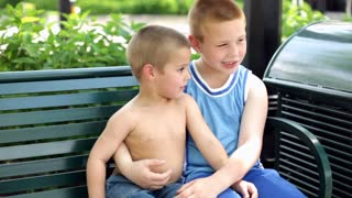 Two cute Boys sitting on park bench