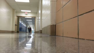 Two kids walking down school hallway
