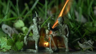 Two plastic army men burning in grass