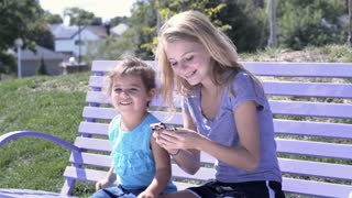 Two young girls playing game on cell phone in park 4k
