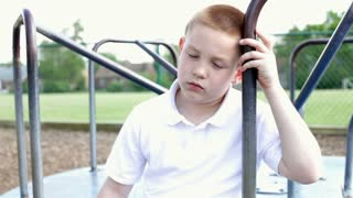 Upset boy leaning head on merry go round