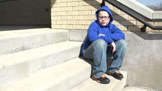 Upset boy on stairs pan shot
