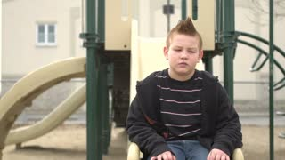 Upset boy sitting on slide