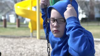 Upset boy sitting on swing