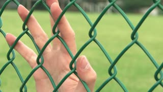 Upset Hands on Fence