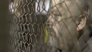 Upset man locked behind fence looking in despair 4k