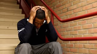 Upset Man Sitting in Stairwell