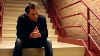 Upset man thinking while sitting on steps
