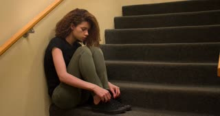 Upset woman sitting in stairwell thinking 4k