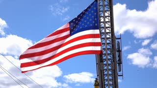 USA Flag in front of blue sky hanging from firetruck ladder 4k