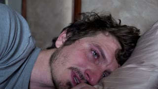 Very upset man crying in bed