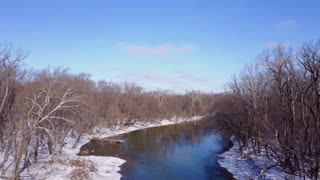Aerial view going over stream in winter forest 4k