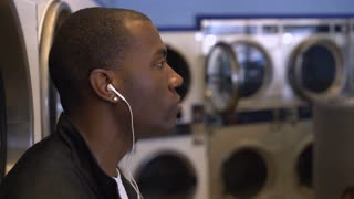 African American male waiting at laundromat while listening to music 4k