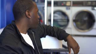 African American male waiting for clothes to wash at laundromat 4k