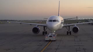 Airport tarmac with Allegiant plane being pushed back from terminal 4k