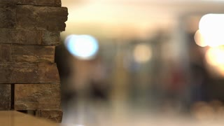 Background of people walking by in airport terminal focus on brick wall 4k