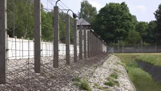 Barbwire fence along prison yard with watch tower in background 4k