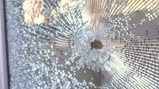 Bullet hole in glass door of business hand held shot 4k
