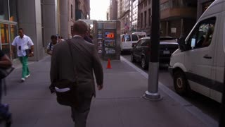 Businessman walking down financial district of New York City