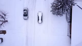 Car driving through snow covered neighborhood aerial view 4k