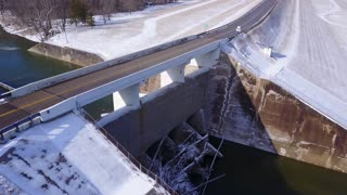 Cars crossing over dam in winter months aerial view 4k