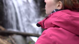 Confident girl looking into distance with waterfall in background 4k