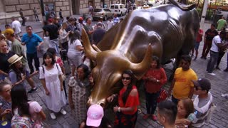 Crowds of people posing with Bull in Financial District NYC