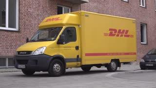 Deutsche Post DHL delivering outside of building in Munich Germany 4k