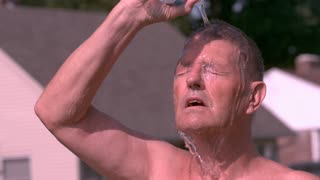 Elderly man in hot sun pouring water on head slow motion