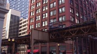 Elevated train going through city streets of Chicago 4k