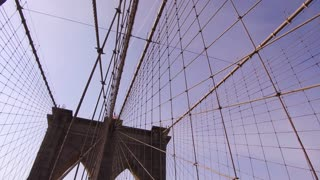 Establishing shot of Brooklyn Bridge cables down to people