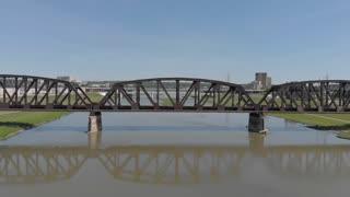 Establishing shot of river behind train bridge fly over