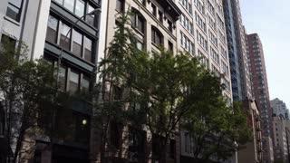 Establishing tilt shot to tall buildings in New York from city street 4k