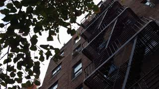 Exterior establishing shot of city apartment complex fire escape 4k