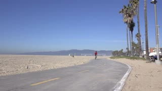 Family on bikes riding by in Venice Beach California 4k