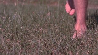 Feet running through grass in extreme slow motion