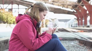 Female sitting on railroad tracks texting on cell phone 4k