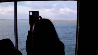 Female tourist taking photo of Statue of Liberty on mobile device 4k