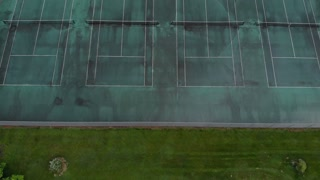 Flying over wet tennis court on cloudy day