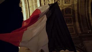 French flag waving in Arc de Triumph Paris
