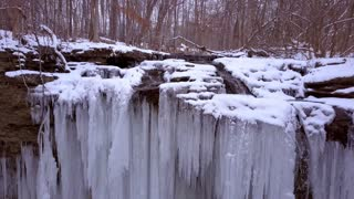 Frozen waterfall with icicles hanging from top aerial view 4k