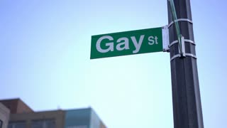 Gay street sign in downtown city evening hours 4k
