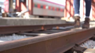 Girl in boots walking along railroad track 4k