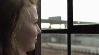 Girl thinking and looking out window into city 4k